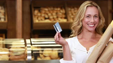супермаркет : Portrait of smiling blonde with paper bags showing credit card in grocery store