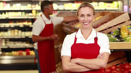 smile : Portrait of smiling worker in front of her colleague in grocery store Stock Footage