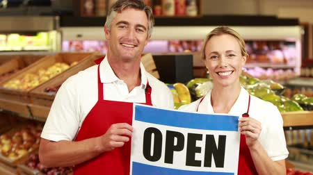 grocery : Portrait of smiling workers holding open sign in grocery store
