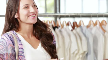 lojas : Pretty brunette paying with card at clothing store in high quality 4k format
