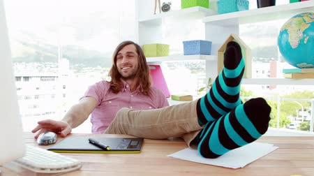 sock : Smiling graphic designer relaxing at desk in the office