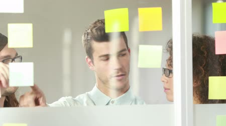 gündelik kıyafetler : Casual business team brainstorming with sticky notes in the office