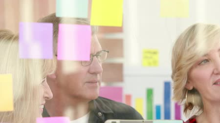 de brainstorming : Businessman writing on sticky note  with his colleagues in office Vídeos