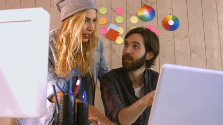 it's cool : Smiling casual designers working over a laptop at the office Stock Footage