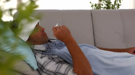 guy home : Sick man lying on sofa under a blanket in ultra hd format Stock Footage