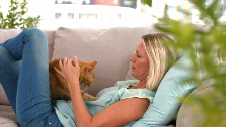 kotki : Happy blonde with pet cat on sofa in ultra hd format Wideo