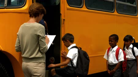 otobüs : Teacher checking list of pupils by bus in ultra hd format Stok Video