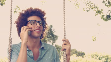 hipster : In high quality format young man in swing on a summers day Stock Footage