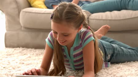 ложь : In slow motion happy girl using digital tablet on rug with mother reading book in background at living area