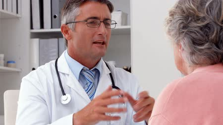 pacjent : Doctor speaking with his patient at desk in ultra hd format