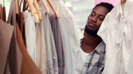 roupas : Male fashion designer looking at rack of clothes in the office