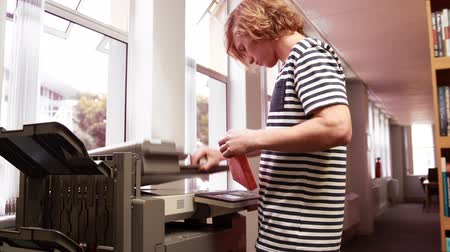 photocopier : Student using a photocopier in the library Stock Footage