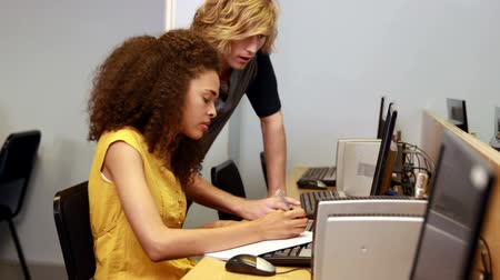 helping : Student helping his friend with computer in the computer room