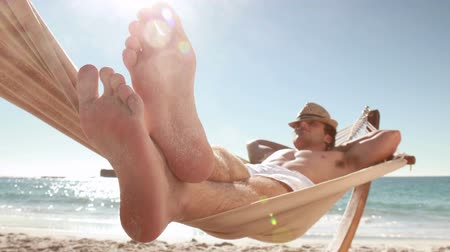 релаксация : Man relaxing in hammock on the beach Стоковые видеозаписи