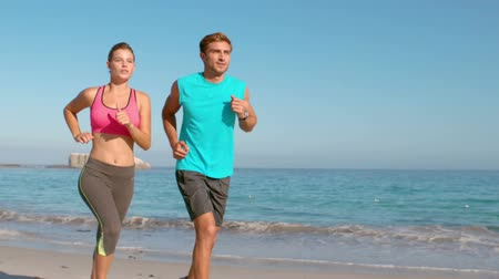 fit : Slow motion of couple jogging on beach with sea view