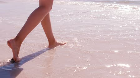 napsütéses napon : Slow motion of woman walking on the sand at the beach on a sunny day