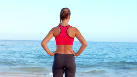 atletika : Fit woman standing on the beach in ultra hd format Dostupné videozáznamy