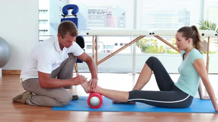 kostka : Physiotherapist using foam roller with patient