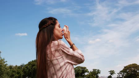 asthma : Pretty brunette using her inhaler on a sunny day