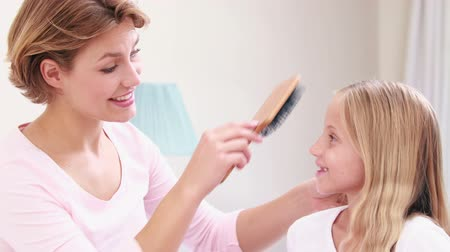 pente : Smiling mother combing hair of daughter in bed