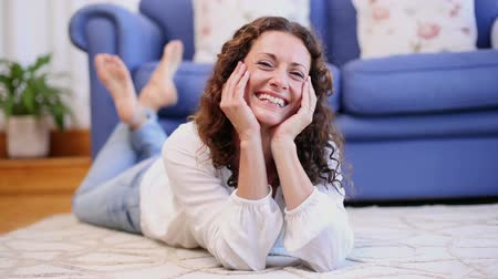 yatarken : Happy woman lying on the rug at home in living room