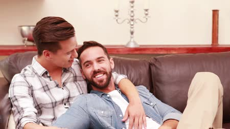 гей : Homosexual couple on the sofa in the living room