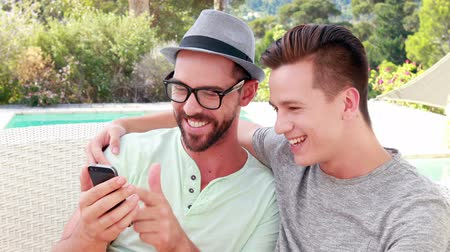 гей : Happy homosexual couple on mobile phone on the garden