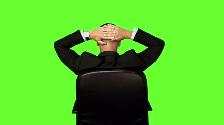 сидеть : Businessman sitting in swivel chair on green screen background Стоковые видеозаписи