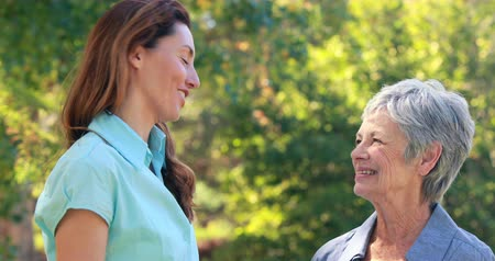 speaking : Happy pretty woman speaking with her grandmother in park