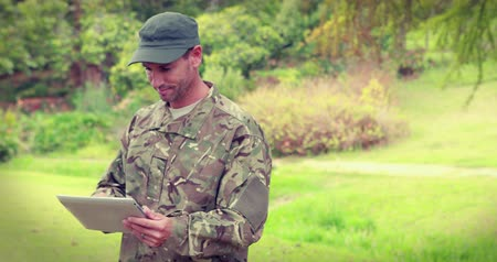 asker : Happy soldier using tablet computer in park