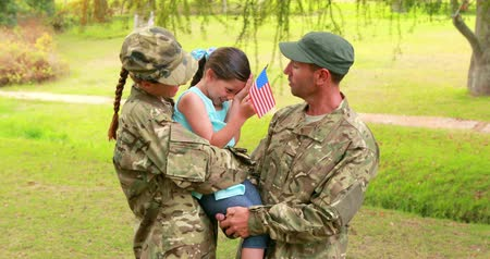 katonai : Couple of soldier reunite with their daughter in park Stock mozgókép
