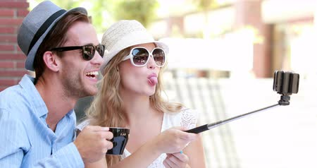 hipster : Cute couple using a selfie stick in high quality 4k format