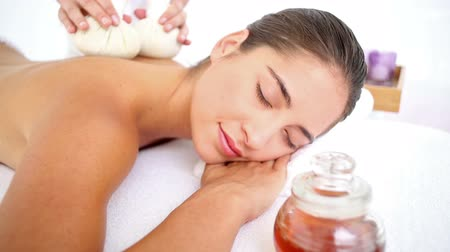 estância termal : Woman enjoying a herbal compress massage at the health spa in slow motion Vídeos