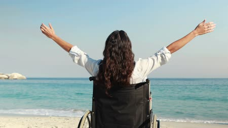 rokkant : Disabled woman with arms outstretched at the beach on a sunny day