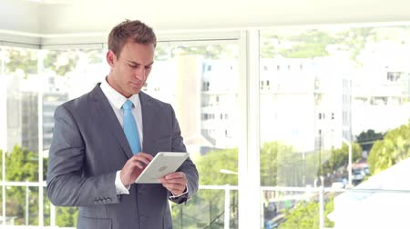 oblek : Smiling businessman using his tablet and looking at camera in the office