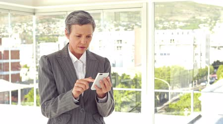 apprehensive : Worried businesswoman using her smartphone in the office