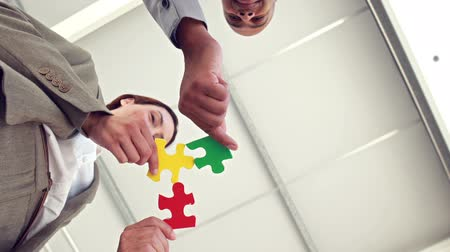 головоломка : Business colleagues holding pieces of puzzle int the office