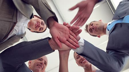 parceria : Business colleagues putting their hands together in the office Vídeos