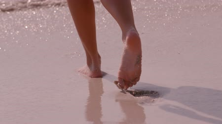 shoreline : Slow motion of a woman walking on the beach bare footed Stock Footage