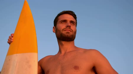 серфер : Shirtless man with a surfboard looking away on the beach