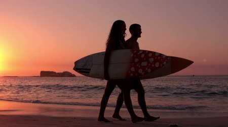 серфер : Cute couple walking on the beach with surfboard in slow motion