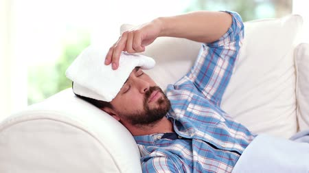 грипп : Sick man taking his temperature on the couch at home in the living room