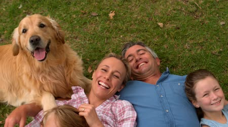 gülümseyen : Happy family smiling at the camera with their dog on a sunny day Stok Video
