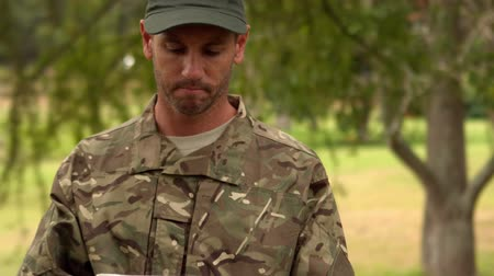 soldados : Soldier looking at tablet pc in park on a sunny day Stock Footage