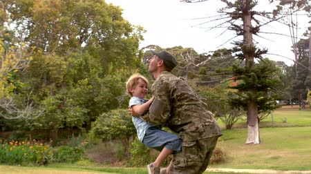 veteran's day : Happy soldier reunited with his son on a sunny day Stock Footage