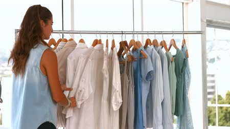 munkaruha : Female fashion designer looking at rack of clothes in the office