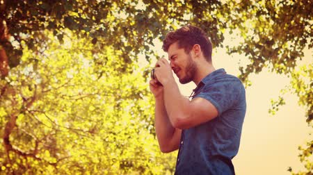 hipster : Close up of man holding retro photo camera in the park on a summer day