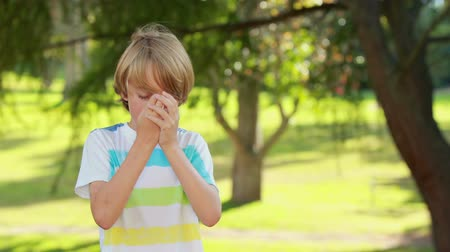 sport dzieci : Little boy using his inhaler in the park on a sunny day