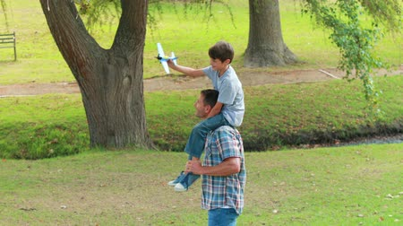 transportar : Father and son having fun in the park on a sunny day