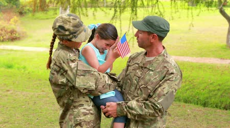 soldados : Couple of soldier reunite with their daughter in park Stock Footage
